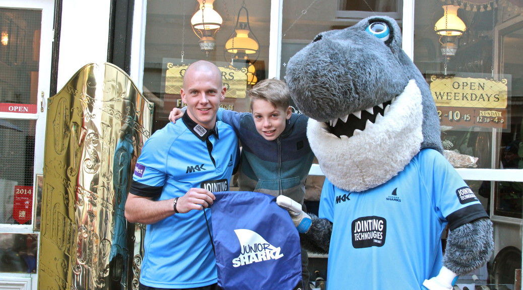Sussex player Lewis Hatchett with Sid the Shark and a Junior Sharkz member