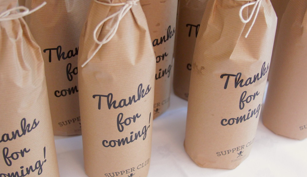 Bottles of wine wrapped in brown paper with 'Thanks for coming!' printed on the outside.